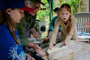 Students making flatbread with wheat they milled.